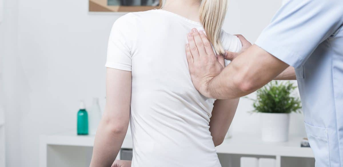 chiropractor with hand on patient's back