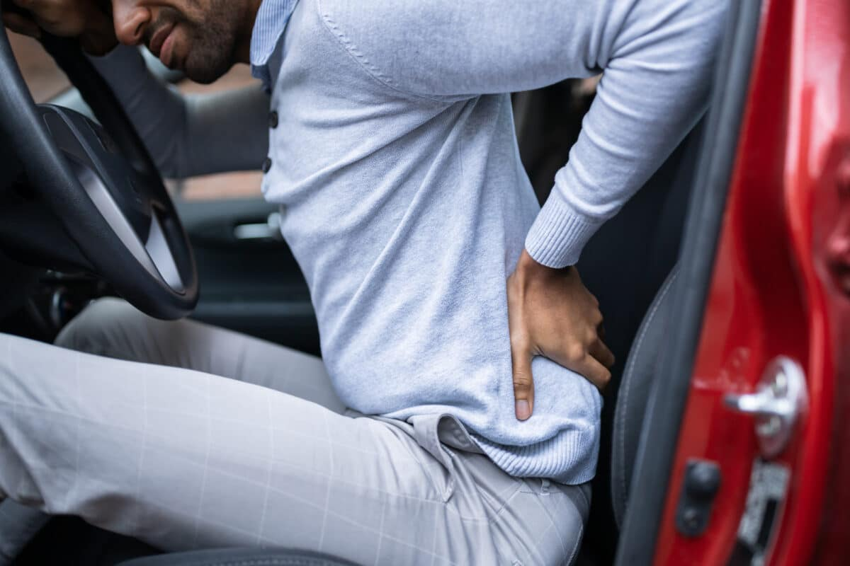man in car holding back in pain