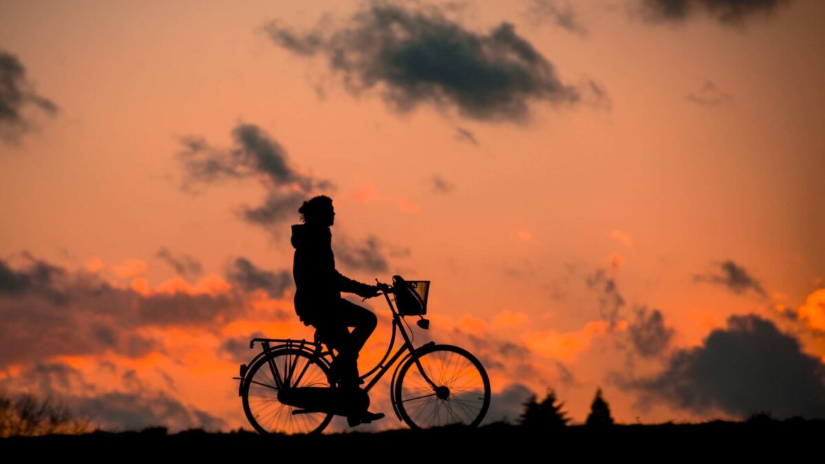 silhouette of person riding bike at sunset