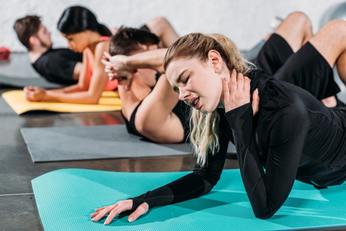 Woman with neck pain in yoga class